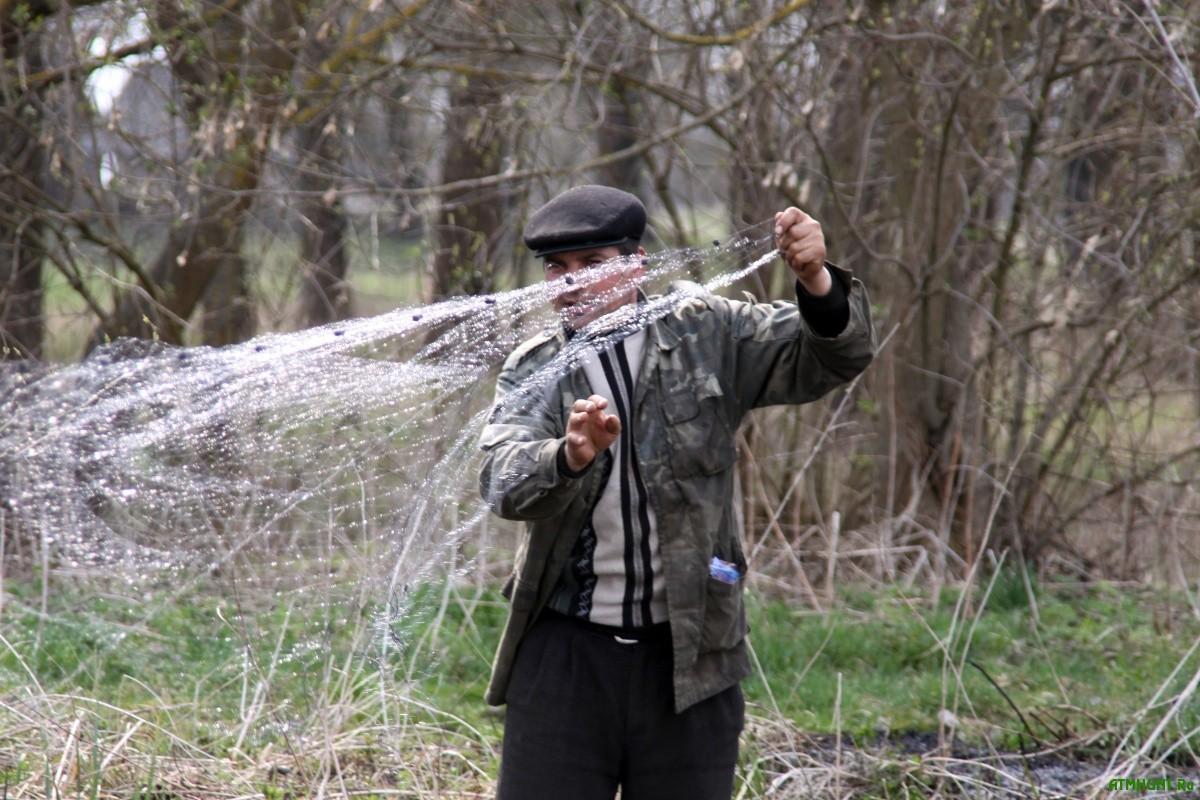 Мужчина закидывает рыболовную сеть